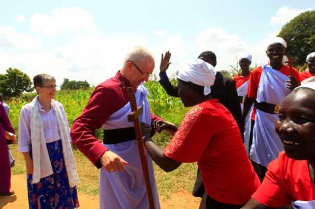 A woman wraps Archbishop of Canterbury Justin Welby in a piece of cloth upon his arrival at Mirieyi settlement camp in Adjumani district during his visit to South Sudanese refugees, Uganda August 2, 2017. REUTERS/James Akena