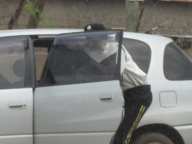 Traffic police officer removing car tint in Juba